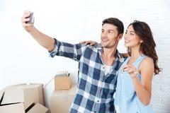 Pares jovenes que hacen el selfie que lleva a cabo llaves en nuevo plano Fotos de archivo