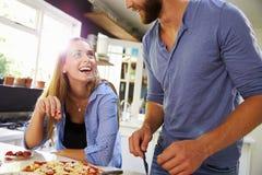 Pares jovenes que hacen la pizza en cocina junta Fotografía de archivo libre de regalías