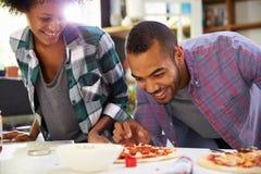 Pares jovenes que hacen la pizza en cocina junta Fotos de archivo libres de regalías