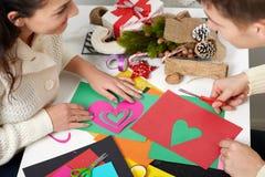 Pares jovenes que hacen las decoraciones de la papiroflexia para el día de San Valentín, la visión superior - romántica y el conc Foto de archivo