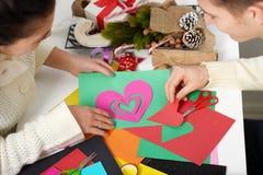 Pares jovenes que hacen las decoraciones de la papiroflexia para el día de San Valentín, la visión superior - romántica y el conc Fotos de archivo