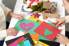 Pares jovenes que hacen las decoraciones de la papiroflexia para el día de San Valentín, la visión superior - romántica y el conc Imagenes de archivo