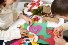 Pares jovenes que hacen las decoraciones de la papiroflexia para el día de San Valentín, la visión superior - romántica y el conc Imágenes de archivo libres de regalías