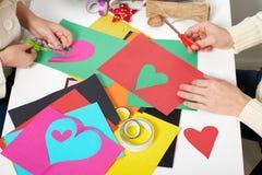 Pares jovenes que hacen las decoraciones de la papiroflexia para el día de San Valentín, la visión superior - romántica y el conc Imagen de archivo libre de regalías