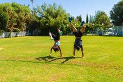 Pares jovenes que hacen las posiciones del pino que entrenan en el parque Imágenes de archivo libres de regalías