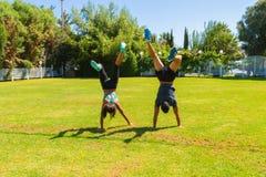 Pares jovenes que hacen las posiciones del pino que entrenan en el parque en verano Imágenes de archivo libres de regalías