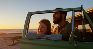 Pares jovenes que hacen una pausa a van window durante puesta del sol en la playa 4k almacen de video