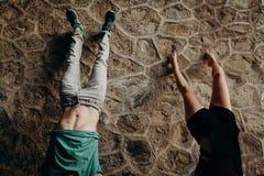 Pares jovenes que hacen una posición de la posición del pino en una pared de piedra Fotografía de archivo libre de regalías
