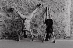 Pares jovenes que hacen una posición de la posición del pino en una pared de piedra Rebecca 36 Imagen de archivo libre de regalías