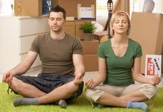 Pares jovenes que hacen yoga en la nueva casa Fotos de archivo