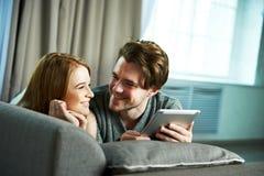Pares jovenes que hojean Internet en una tableta Fotos de archivo libres de regalías