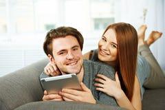 Pares jovenes que hojean Internet en una tableta Fotos de archivo