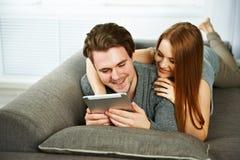Pares jovenes que hojean Internet en una tableta Fotografía de archivo