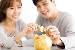 pares jovenes que insertan la moneda en Piggybank Imágenes de archivo libres de regalías