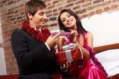 Pares jovenes que intercambian los regalos que intercambian los regalos imágenes de archivo libres de regalías