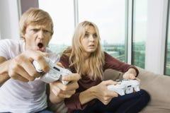 Pares jovenes que juegan al videojuego en sala de estar en casa Imagenes de archivo