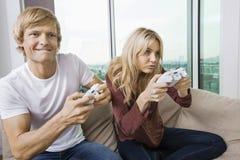 Pares jovenes que juegan al videojuego en sala de estar en casa Imagen de archivo