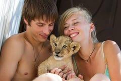 Pares jovenes que juegan con el pequeño cachorro de león Foto de archivo