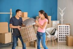 Pares jovenes que juegan con las pertenencia dentro El trasladarse a nueva casa fotos de archivo libres de regalías