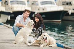 Pares jovenes que juegan con un perro en el puerto Fotos de archivo