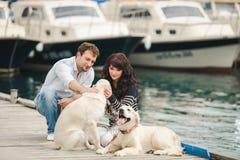Pares jovenes que juegan con un perro en el puerto Imágenes de archivo libres de regalías