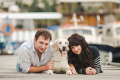 Pares jovenes que juegan con un perro en el puerto Fotos de archivo libres de regalías