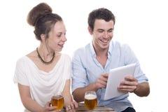 Pares jovenes que juegan con una tableta digital Imagen de archivo