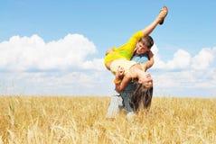 Pares jovenes que juegan en campo asoleado del trigo Imagenes de archivo