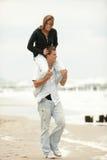 Pares jovenes que juegan en de lengüeta de la playa Fotografía de archivo libre de regalías
