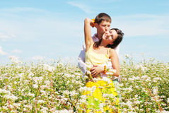 Pares jovenes que juegan en el campo de flores Fotografía de archivo