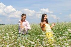 Pares jovenes que juegan en el campo de flores Imagenes de archivo