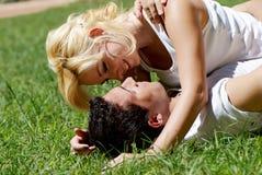 Pares jovenes que juegan en el parque en hierba Imagen de archivo libre de regalías