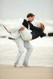 Pares jovenes que juegan en la playa Imagen de archivo libre de regalías
