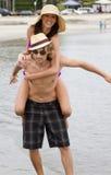 Pares jovenes que juegan en la playa Imagen de archivo