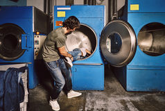 Pares jovenes que juegan en un lavadero industrial Imágenes de archivo libres de regalías
