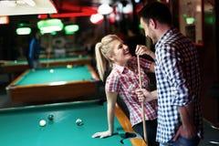 Pares jovenes que juegan junto al billar en barra Foto de archivo libre de regalías