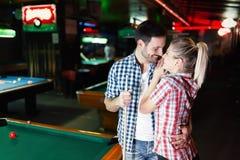 Pares jovenes que juegan junto al billar en barra Fotografía de archivo libre de regalías