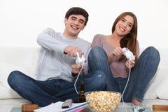 Pares jovenes que juegan los juegos de ordenador Foto de archivo libre de regalías
