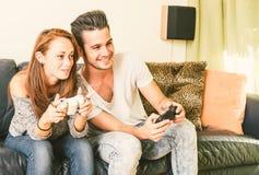Pares jovenes que juegan a los juegos video Imagen de archivo libre de regalías