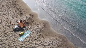 Pares jovenes que juegan m?sica y que cantan junto en la playa almacen de metraje de vídeo
