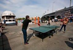 Pares jovenes que juegan a tenis de mesa en un festival de la cultura de la calle Imagen de archivo libre de regalías