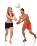 Pares jovenes que juegan a voleibol Imagenes de archivo