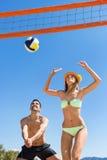 Pares jovenes que juegan a voleibol Imagen de archivo libre de regalías