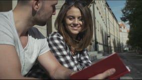 Pares jovenes que leen junto mientras que se sienta en las escaleras de la universidad, al aire libre metrajes