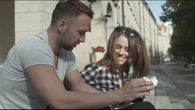 Pares jovenes que leen junto mientras que se sienta en las escaleras de la universidad, al aire libre almacen de video
