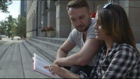 Pares jovenes que leen junto mientras que se sienta en las escaleras de la universidad, al aire libre almacen de metraje de vídeo