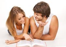 Pares jovenes que leen un libro Imagenes de archivo