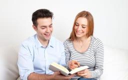 Pares jovenes que leen un libro Imagen de archivo