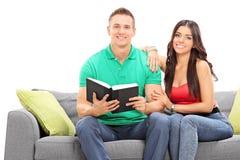 Pares jovenes que leen un libro asentado en el sofá Imágenes de archivo libres de regalías