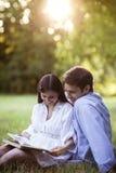 Pares jovenes que leen un libro en un parque Imagen de archivo